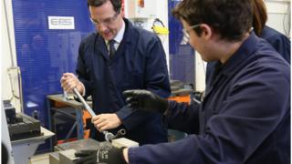 George Osborne uses a wrench with the guidance of apprentice James Spence