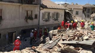 Rescuers look through rubble