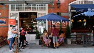 People sit at a restaurant with outdoor seating in the Little Italy neighbourhood on June 24, 2020 in New York City
