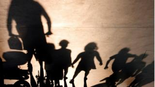Shadowy adult with shadowy children