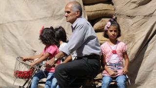 Üç kızı bisiklette taşıyan bir Suriyeli