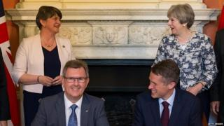 Theresa May and Arlene Foster witness the signing of the Conservative-DUP pact