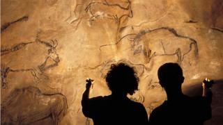 Silhouettes of two people holding up oil lamps to illuminate cave paintings