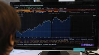 A trader looks at his screen as prices rise