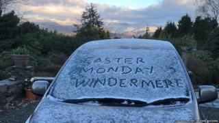 """Easter Monday Windermere"" written on the windscreen on a frost-covered car with cloud-topped hills in the background"