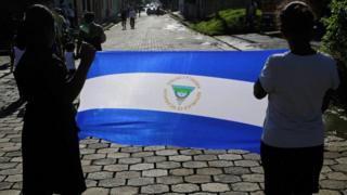 Dos mujeres sosteniendo una bandera de Nicaragua durante un funeral.
