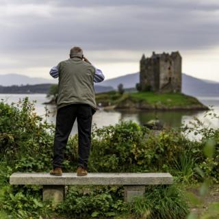 Man taking picture of Stalker Castle.