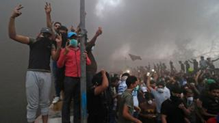 Protesters pose amid smoke near a burning building in Basra, 6 September 2018