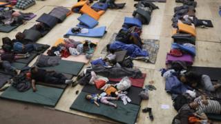 Migrantes deitados em colchonetes