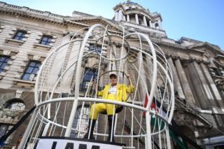 in_pictures Dame Vivienne Westwood suspended in a large bird cage outside the Old Bailey in London