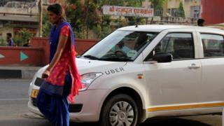 A lady walks past an Uber cab in India