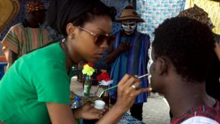 An artist paints the face of a man during the Chale Wote street art festival in Accra, on August 21, 2016
