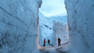 Workers cut through snow wall on the Bessans to Bonneval-sur-Arc road in France
