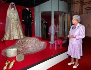 Королева Елизавета смотри на свадебное платье на выставке