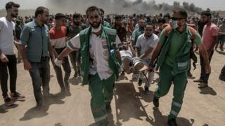 Palestinian medics carry a wounded protester near the border with Israel in the east of Jabaliya in the northern Gaza Strip, 14 May 2018