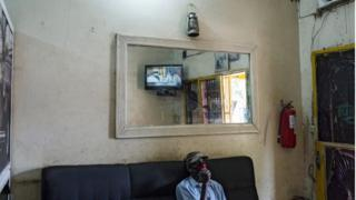 A man watches local TV coverage of resignation of Malian President Ibrahim Boubacar Keita at a printing shop near the Independence Monument in Bamako, Mali.