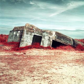 Infrared photograph of a bunker, surrounded by plants and sand