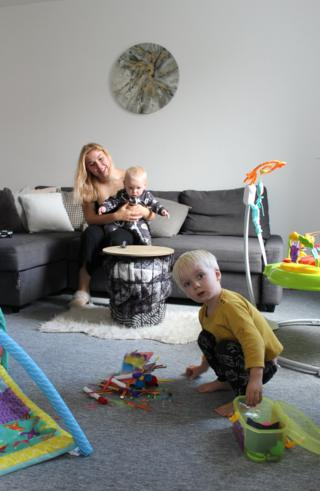 A mother sits on the sofa holding her baby as her toddler plays with his toys on the floor