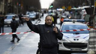 パリ北部の事件現場から車両を迂回させる警官(7日)