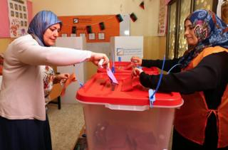 A Libyan woman casts her ballot at a polling station during legislative elections in the capital Tripoli on June 25, 2014. Polling was under way across Libya in a general election seen as crucial for the future of a country hit by months of political chaos and growing unrest.