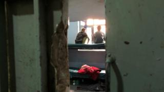 Two boys sit on a bunkbed in a cell