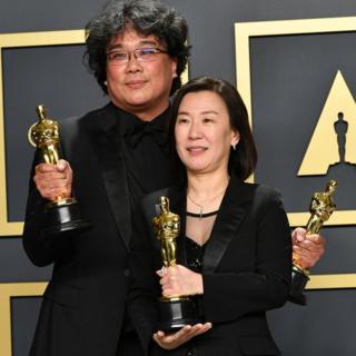"""El director Bong Joon-ho y la productora Kwak Sin-ae de la película """"Parasite"""" posan para los fotógrafos con sus respectivos Oscar."""