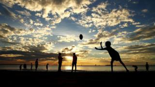 Boys play sport on a beach in the Northern Territory