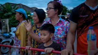 Onlookers watch and cheer as ambulances transport the 10th rescued schoolboy from a helipad nearby to Chiangrai Prachanukroh Hospital on July 10, 2018 in Chiang Rai, Thailand
