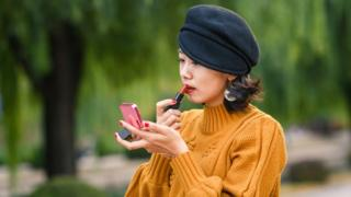 A young Chinese woman putting on make-up
