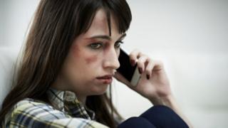 File photo of abused woman phoning helpline.