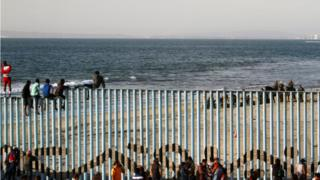 Migrants, part of a caravan of thousands trying to reach the US, gather at the border fence between Mexico and the United States after arriving in Tijuana
