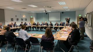 Over 20 taskforce members holding a meeting around a set of tables