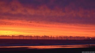 Red sky by a wind farm