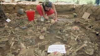 Forensic anthropologist Claudia Bernard brushes dirt from human remains in El Mozote, El Salvador (October 1992)