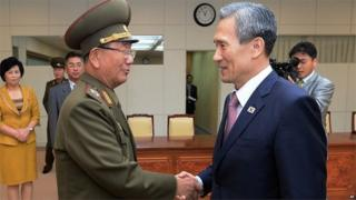 South Korean presidential security adviser Kim Kwan-jin (R) shakes hands with senior North Korean official Hwang Pyong So in Panmunjom (25 Aug 2015)
