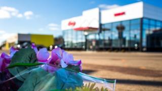父親と息子が犠牲になった自動車販売店の前に花が手向けられた