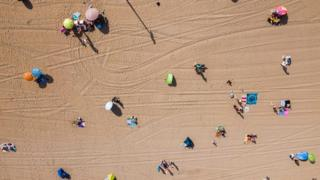 An aerial photo of the first beach-goers on the beach of Scheveningen in the Netherlands