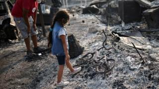sports A little girl looks at a burnt bicycle in Phoenix, Oregon