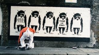 Umetnik ispred Benksijevog rada