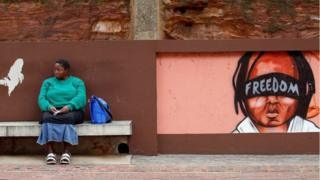 A woman sits next to murals as opposition parties march for the removal of President Jacob Zuma outside the Constitutional Court in Johannesburg, South Africa, May 15, 2017.