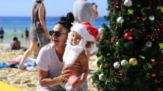 Families pose by a Christmas tree on Bondi Beach on December 25, 2018