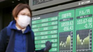 Woman walks past Tokyo stock market board (12/03/2020).