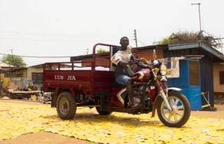 A vehicle on a yellow tapestry created by artist Serge Attukwei Clottey on a road in La - Accra, Ghana