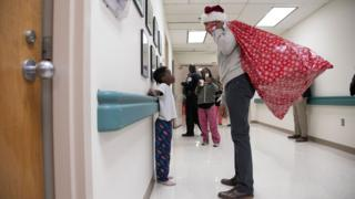 Keçmiş ABŞ prezidenti Barack Obama uşaq tibbi mərkəzində Santa Claus papağında uşaqlara hədiyyə paylayır və onların valideynlərini salamlayır - Washington DC, 19 dekabr 2018