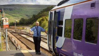 northern rail train with driver standing next to it