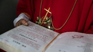 A Chinese Catholic deacon holds a bible at the Palm Sunday Mass during the Easter Holy Week, 19 April 9 2017