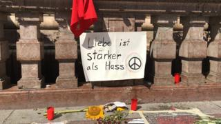 "Sign reading ""Love is stronger than hate"" in German, above candles and flowers, in central Munich"