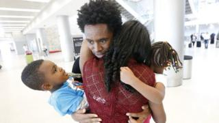 Olympic silver medallist Feyisa Lilesa, rear, of Ethiopia, hugs his wife Iftu Mulia, his daughter Soko, right, five, and son Sora, left, three, while picking up his family at Miami International Airport, Tuesday 14 February 2017, in Miami, the US