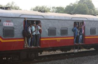 People hang onto local trains as the commuter train enters Mumbai