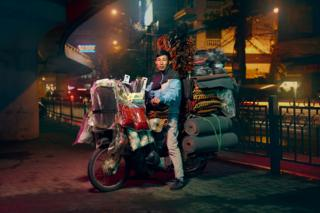 A man is posed on a motorcycle which is over spilling with car accessories such as mats and beaded seat cover